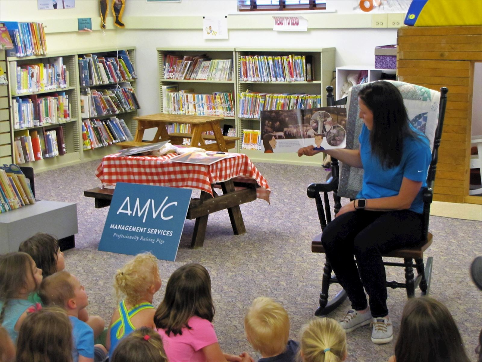 AMVC public relations coordinator, Alicia Humphrey, reads a non-fiction pig story to the group.