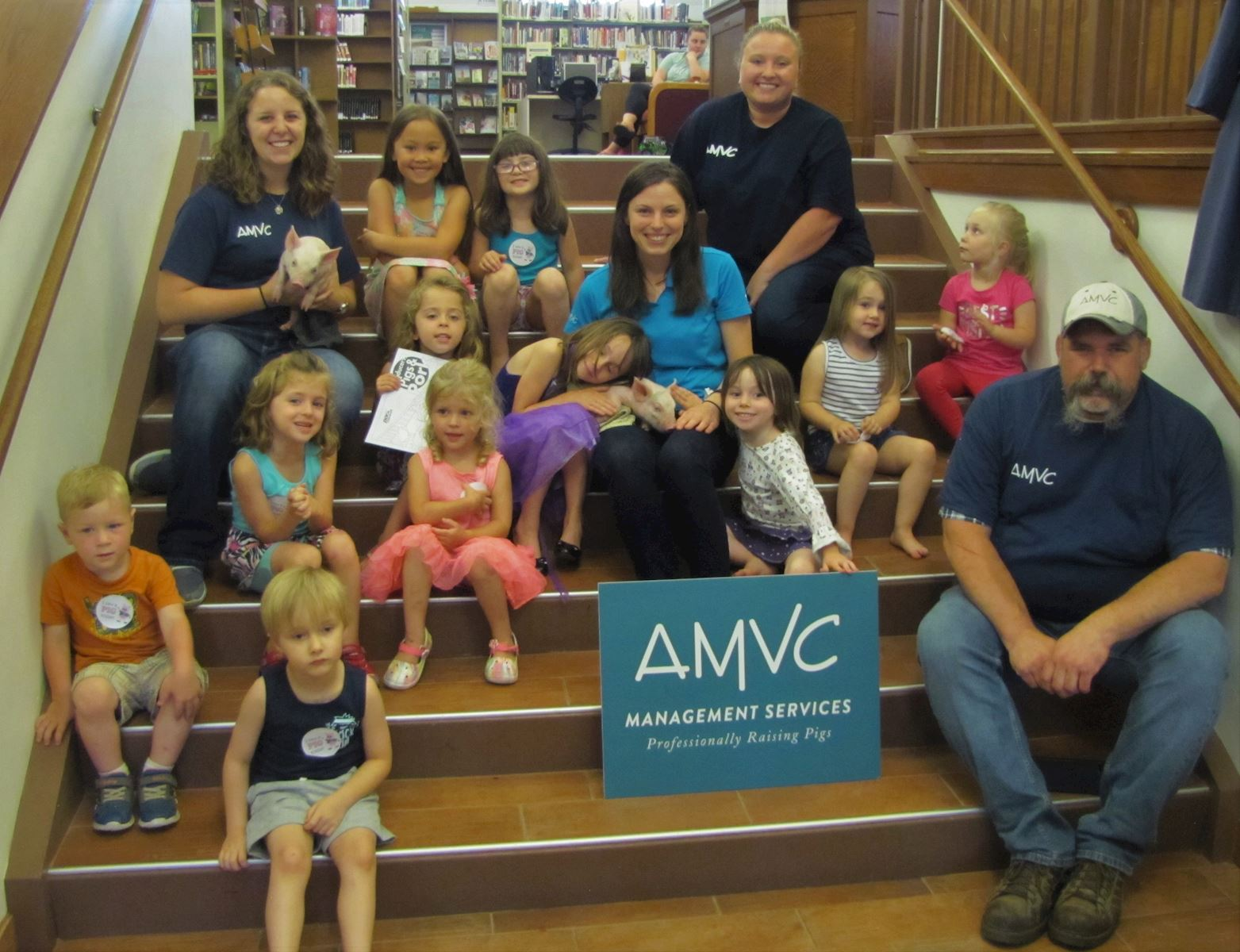 AMVC employees pose with some of the children that attended the Piglet Storytime at the Colfax-Perry
